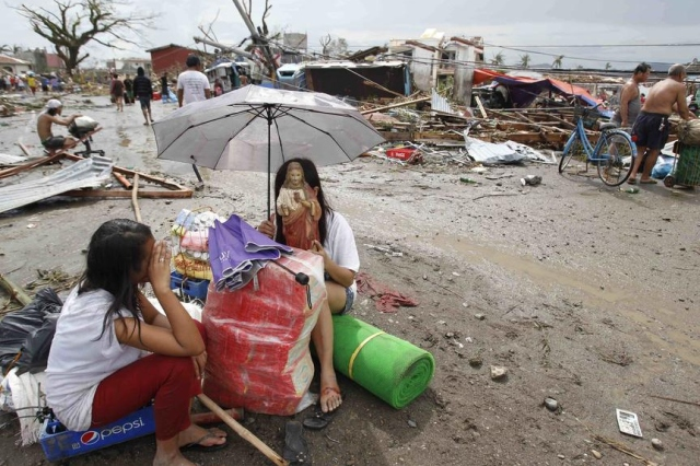 A survivor holds a statue of Jesus Christ, her only saved belonging, after the typhoon.