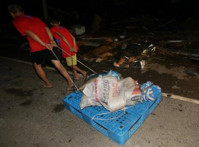 Residents pull relief goods by dead bodies in the street.