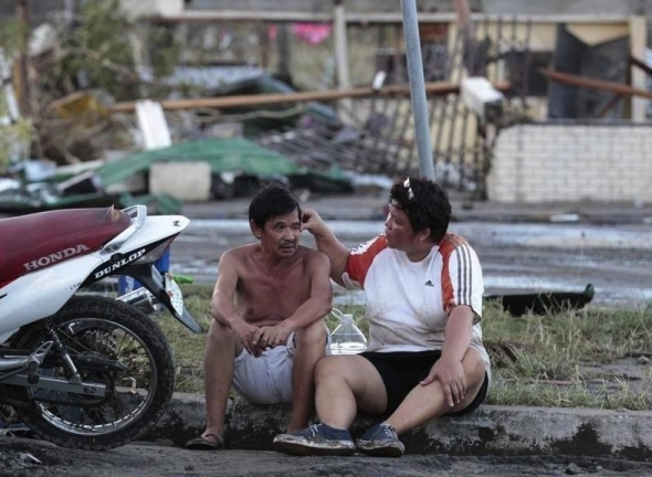 Residents sit on a curb outside their damaged house.