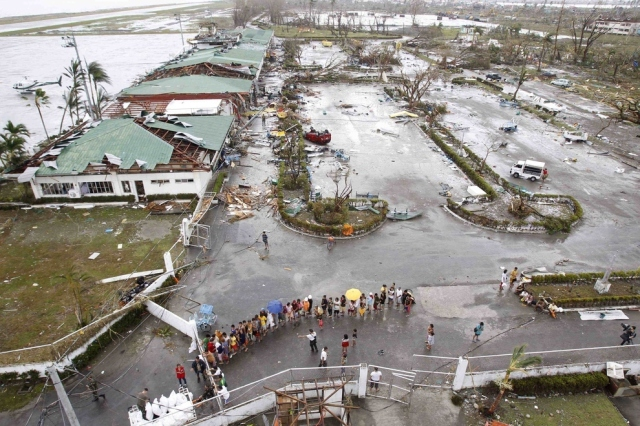 Residents wait near Tacloban's damaged airport for relief goods on Nov. 9.