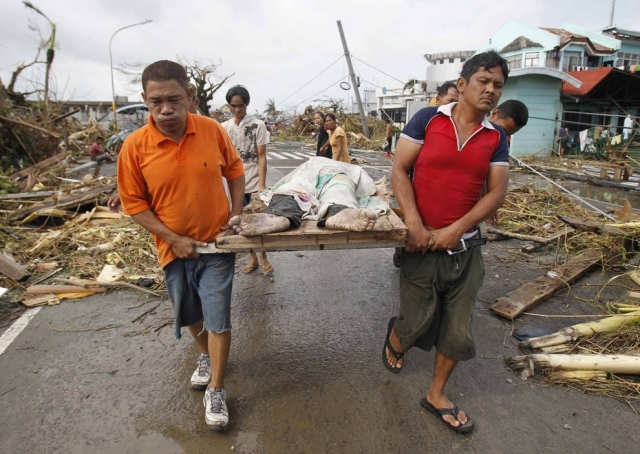 Survivors carry a person killed in the storm.