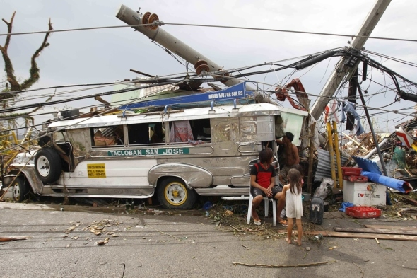 Survivors who lost their homes use a Jeepney public bus as shelter.
